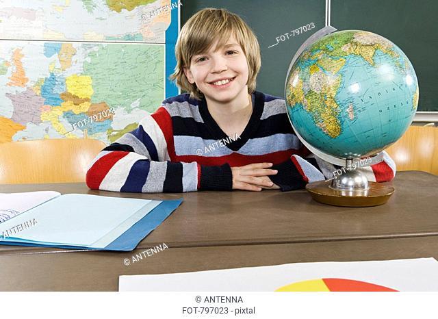 Portrait of a schoolboy sitting near a globe