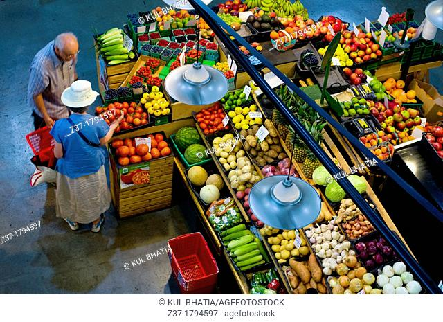 A couple shopping at an indoor market for fresh fruit and vegetables, Ontario, Canada