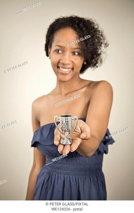 Young black woman holding a very small trophy cup