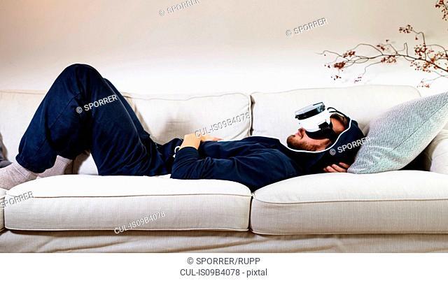Mid adult man lying back on sofa watching virtual reality headset