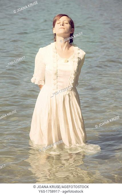 a woman in a white, Victorian dress is standing in the water and enjoying the sun