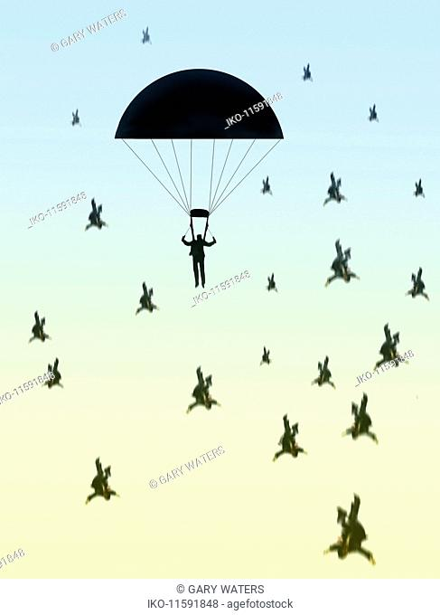 Businessman safe in parachute while others fall through the air