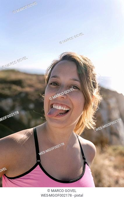 Spain, Asturias, portrait of a sportswoman, smiling, sticking out tongue