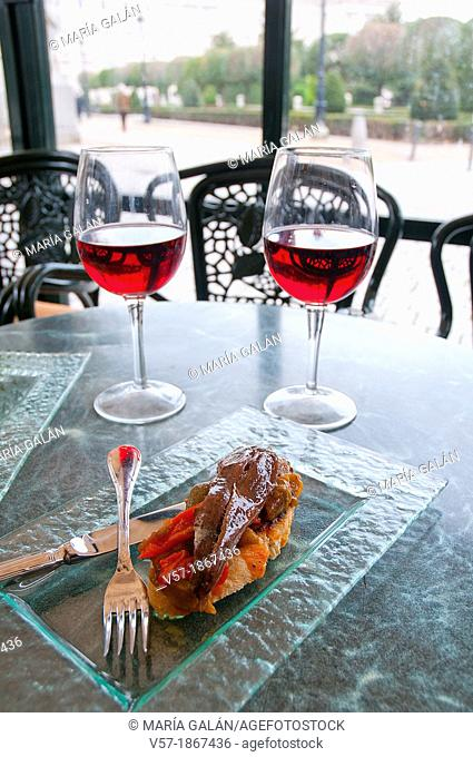 Spanish appetizer: two glasses of rose wine with tapa of anchovy fillet with red pepper. Oriente Square, Madrid, Spain