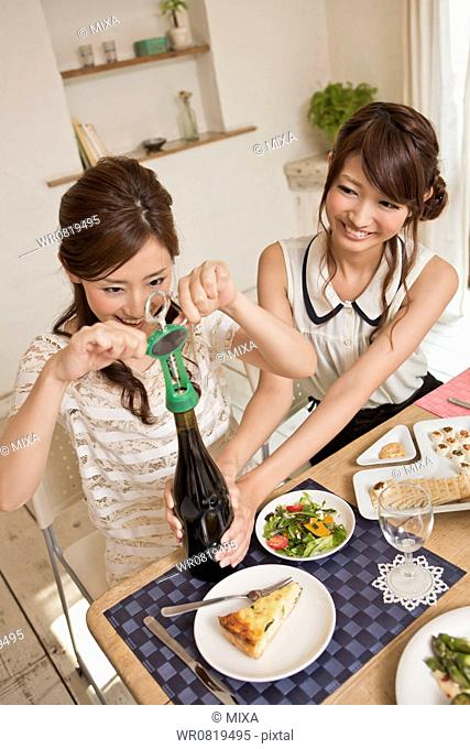 Two Young Women Opening a Wine Bottle