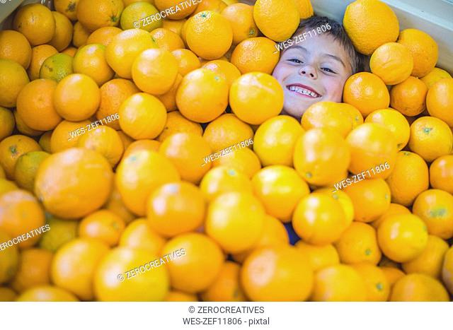 Boy lying under pile of oranges