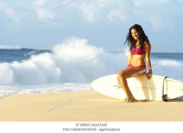 Hawaii, Oahu, surfer girl on beach in swimsuit with surfboard