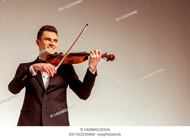 The young musician man playing violin on gray background