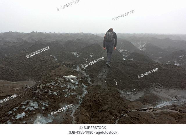 Hiker traversing ash covered ground near the summit of the Eyjafjallajokull Volcano in Iceland one year after the eruption
