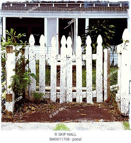 A worn and weathered wooden fence in front of an abandoned house in Florida
