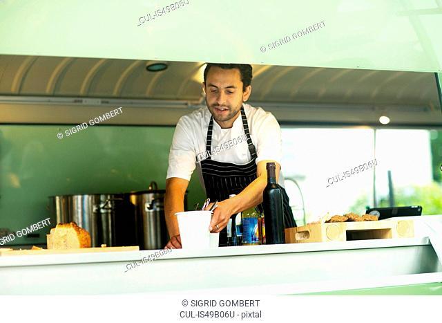 Small business owner preparing food in van food stall