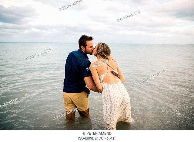Rear view of couple knee deep in water kissing
