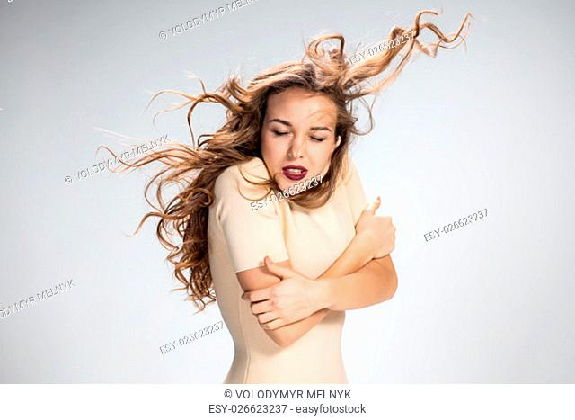 The woman with her hair blowing in the wind on gray