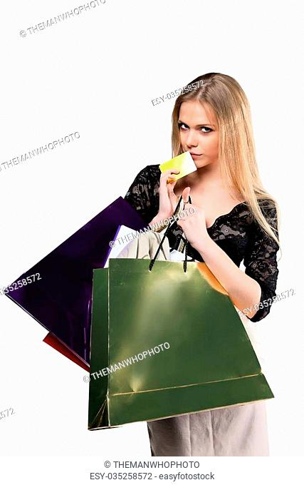 Young girl with paper bags and credit card isolated on white background
