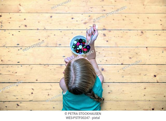 Girl lying on plank floor with bowl of flower heads, top view