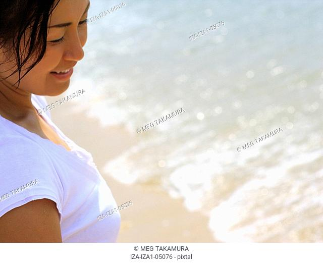 Close-up of a mid adult woman standing on the beach and smiling