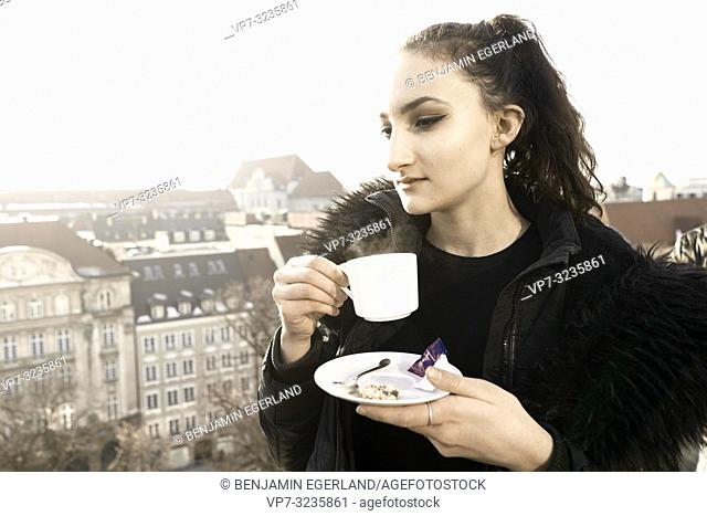 woman holding warm coffee cup outdoors in city Munich, Germany