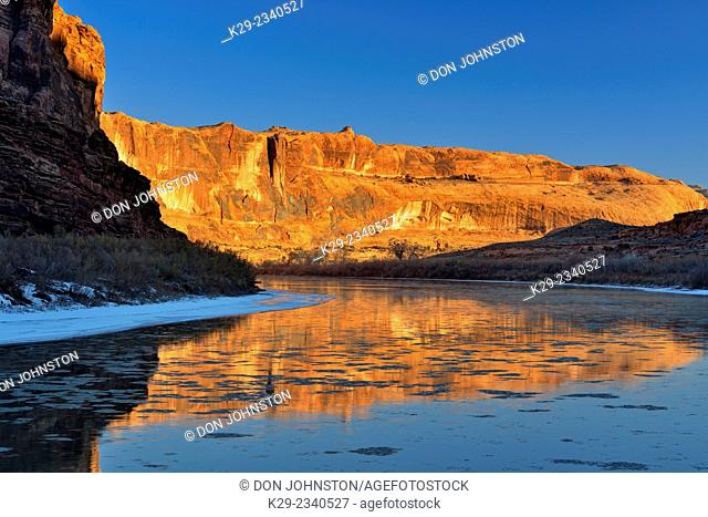 Sandstone walls reflected in the Colorado River at dawn during winter, Colordao Riverway Recreation Area Moab, Utah, USA