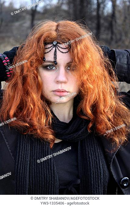 red haired girl outdoors with diadem in hairs