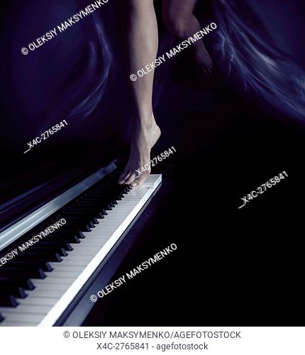 Woman bare legs dancing on a piano keyboard, music and dance artistic dream-like concept