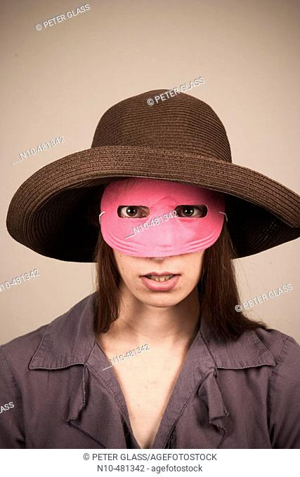 Young woman, wearing a hat and pink mask, posing