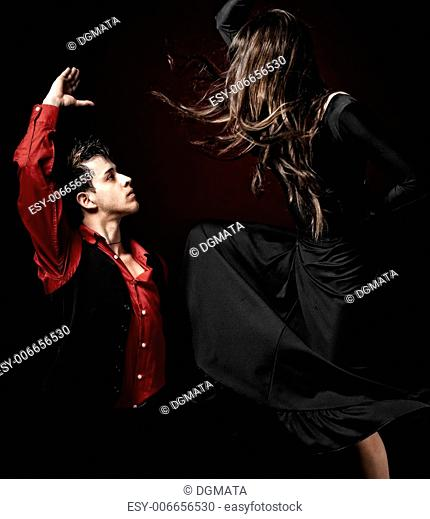High contrast Young couple passion flamenco dancing on red light background