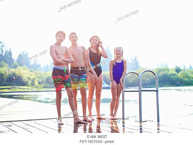 Portrait tween friends in bathing suits standing on sunny lake dock
