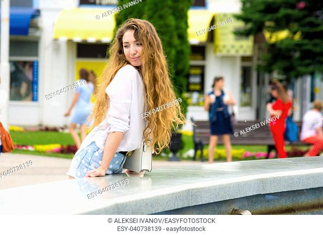 Beautiful young girl examines passers by the fountain in the park