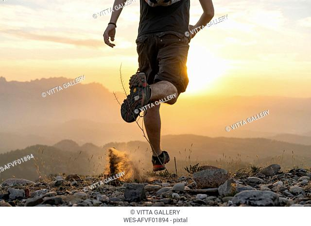 Spain, Barcelona, Natural Park of Sant Llorenc, man running in the mountains at sunset