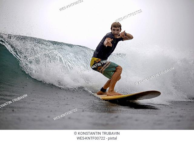 Indonesia, Java, man surfing and posing