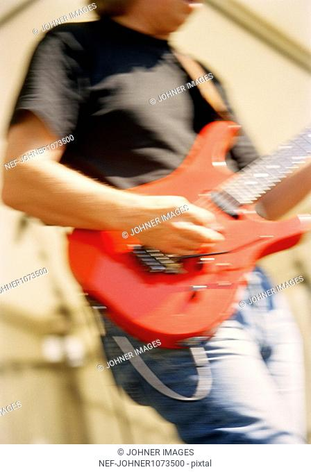 Man playing red electric guitar