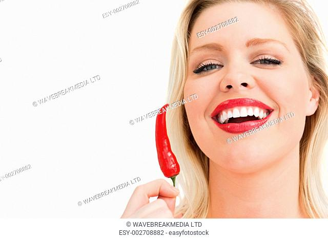 Blonde woman holding a chili while laughing against a white background