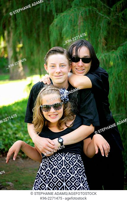 Three siblings smiling outdoors in a park for the camera