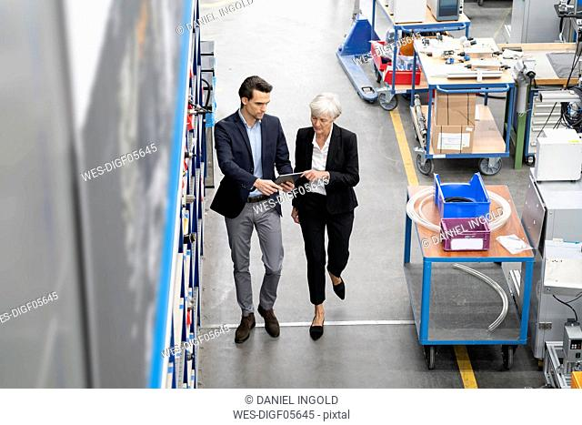 Businessman and senior businesswoman with tablet walking in a factory