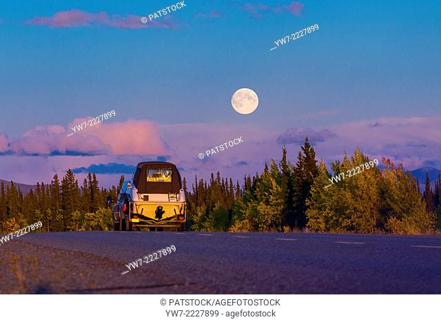 Car on Alaska Highway during full moon, USA