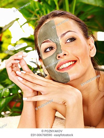 Happy woman getting facial mask in tropical beauty spa
