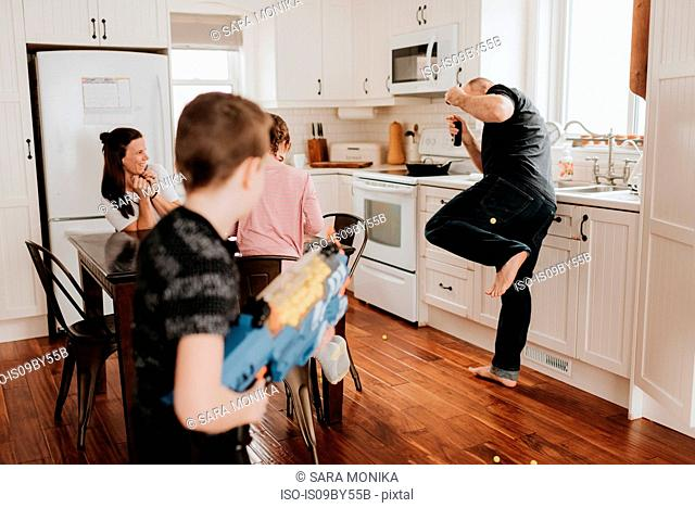 Boy shooting father with foam ball gun in kitchen