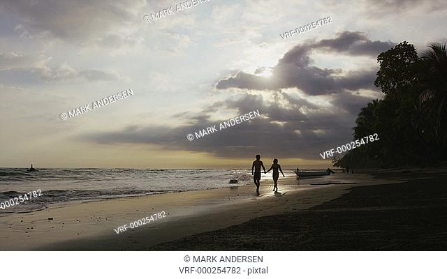 Slow motion wide shot of couple walking on beach at sunset / Esterillos, Puntarenas, Costa Rica