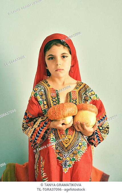 Female youth in colourful dress with red headess sitting alone holding gourd