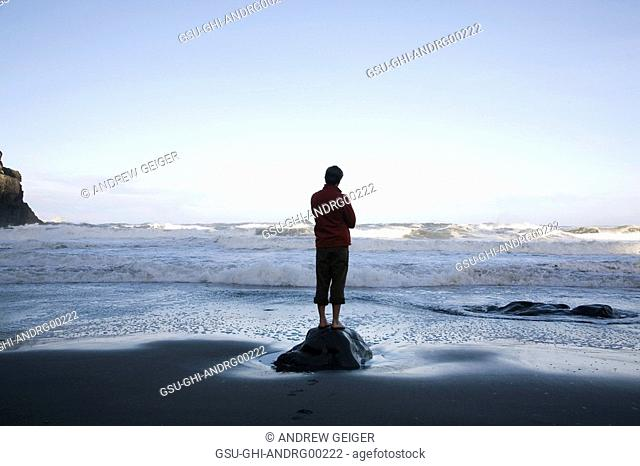 Lone Man Standing on Rock at Beach