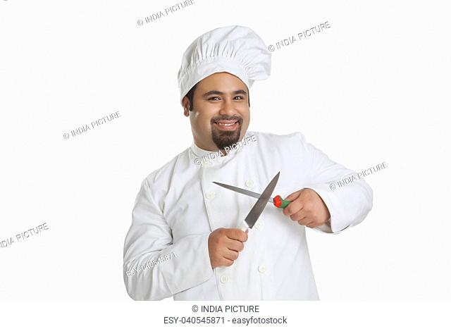 Portrait of chef sharpening knives
