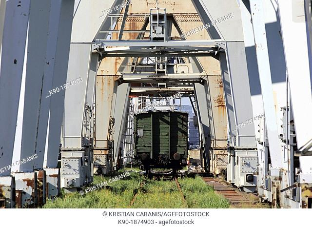 Rail car under an alley of old, rusty cranes, Hamburg, Germany, Europe