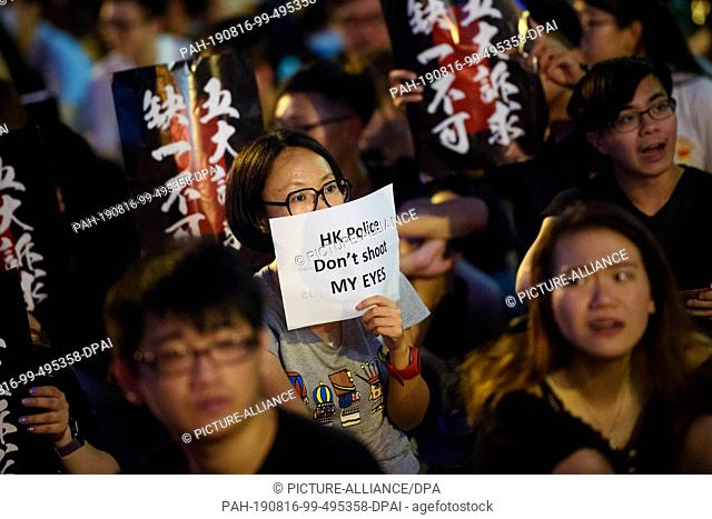"16 August 2019, China, Hongkong: During a protest rally in front of the Chater Garden in Central County, a participant holds a sign with the inscription """"HK..."