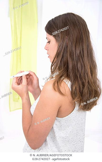 Young woman holding a self testing pregnancy test, at home