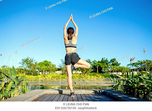 Woman doing yoga pose in park