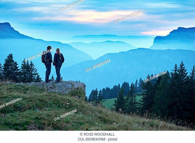 Hikers enjoying view of misty mountains, Manigod, Rhone-Alpes, France
