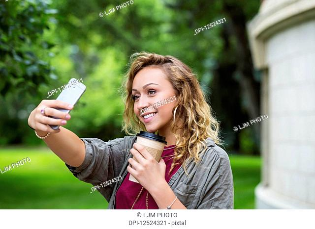 A beautiful female university student taking a self-portrait with her smart phone on the campus; Edmonton, Alberta, Canada
