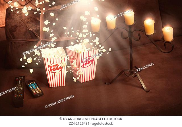 Creative still life home entertainment photo of overflowing retro movie popcorn box with candle backlit by film projector on comfy lounge chair