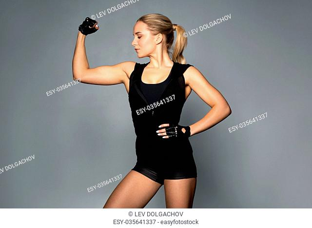 sport, fitness and people concept - young woman posing and showing muscles in gym