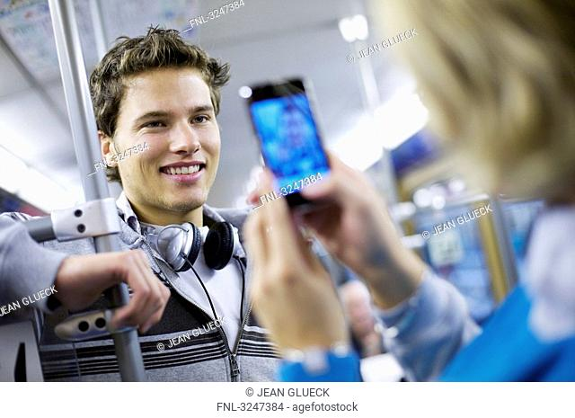 Young man in metro getting photographed with camera phone, slanted view